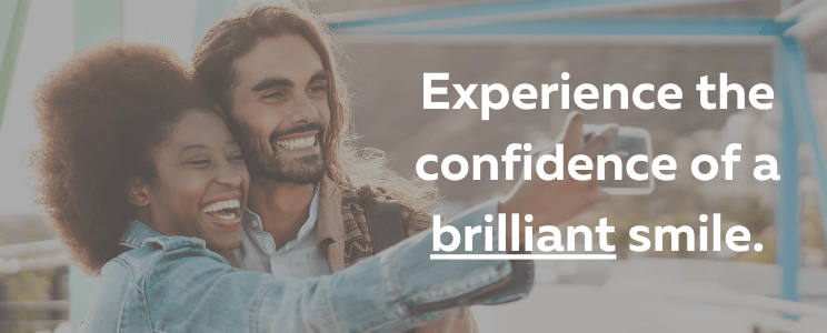 Couple taking selfie with overlay of words that say Experience the Confidence of a Brilliant Smile