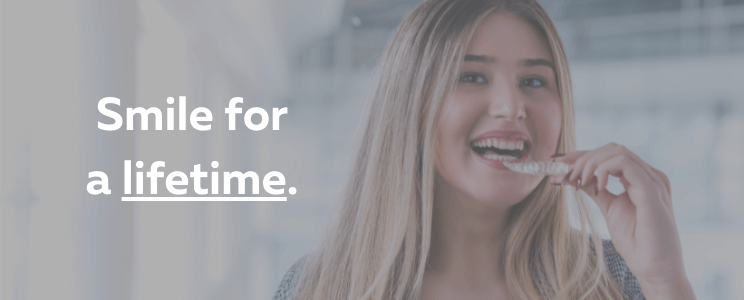Smiling woman with aligner with overlay of words that say Smile for a Lifetime