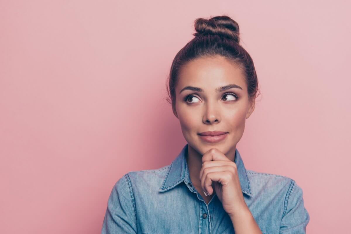 Portrait of a woman with her hair styled in a bun thinking and looking off to the side in front of a pink background.