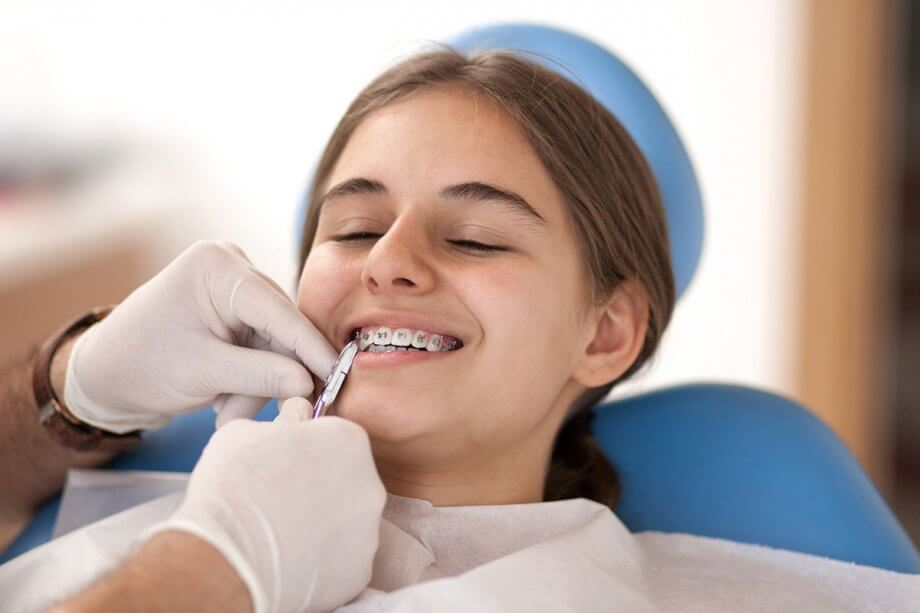 girl in orthodontist chair getting an adjustment