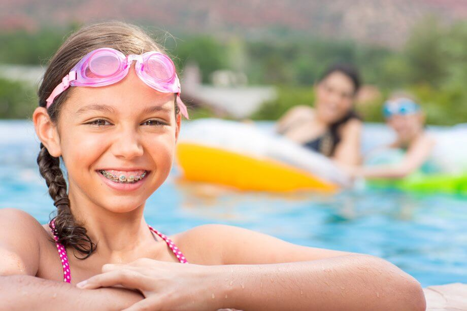 young girl in pool with goggles on wearing braces