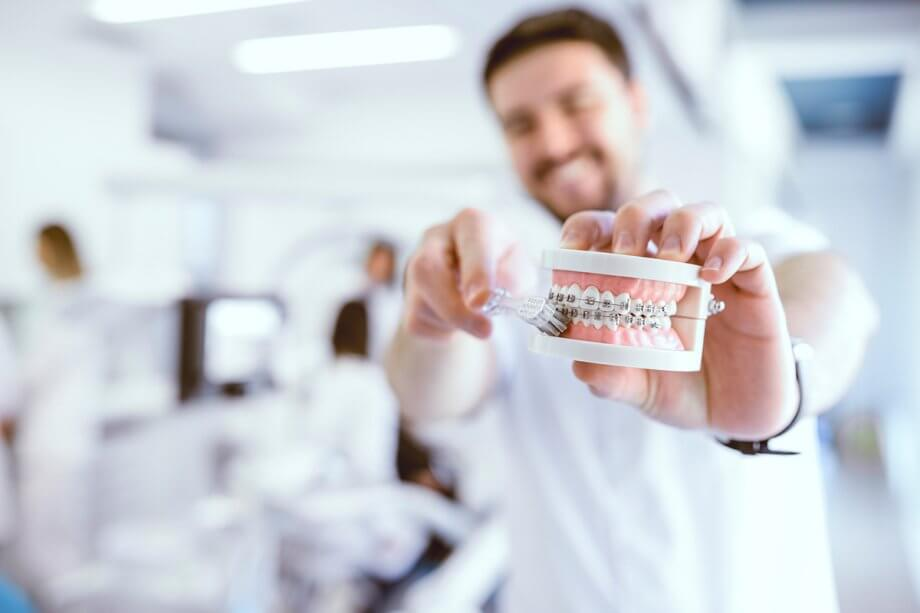 man holding dental model showing how to brush teeth