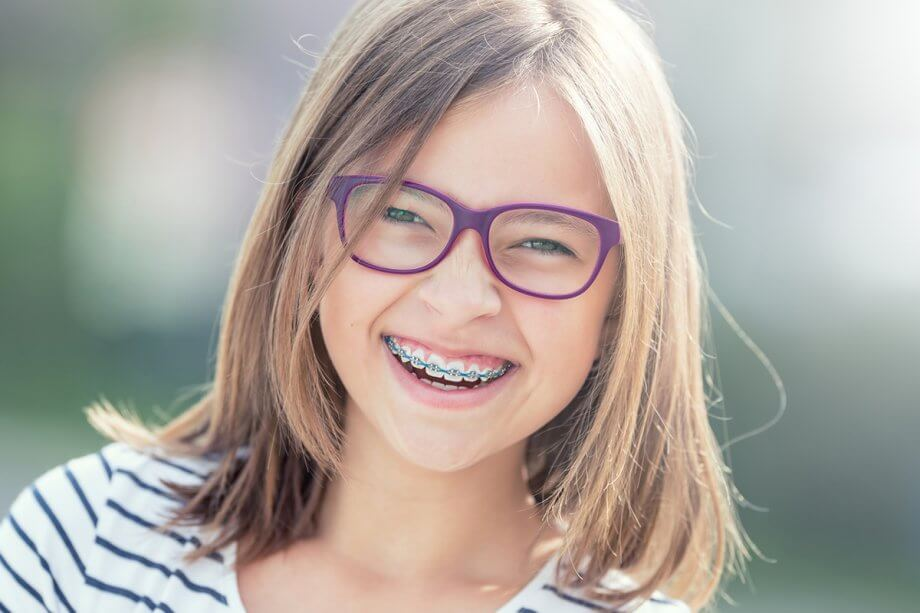 young smiling girl with braces and purple glasses