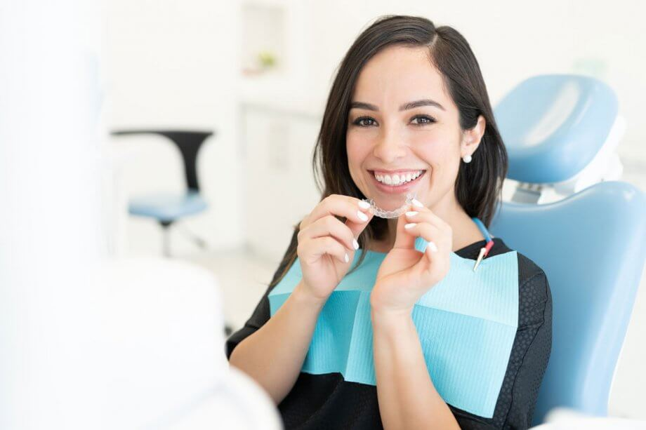 woman in dental chair putting in invisalign